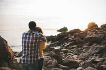 couple hugging on a beach looking out at the ocean
