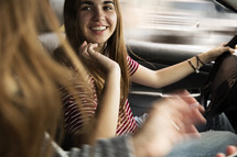 a teen girl talking to a passenger while driving