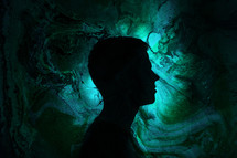 silhouette of a man standing in green swirling light