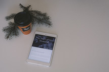 Bible app on an iPad, coffee cup, and pine boughs