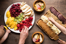 people eating fruit and a meat and cheese platter