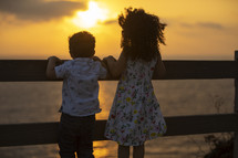 kids looking over a railing at the setting sun