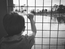 toddler boy looking out a window at a fountain in a pond