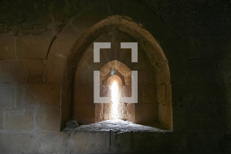 sunlight through a window in ruins at an historic site in Jordan