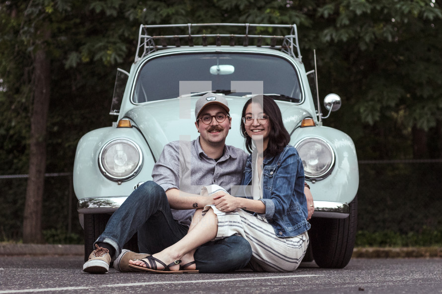 a couple sitting in front of a vintage Volkswagen Beetle