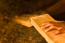 sawing a wooden board in two