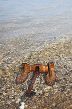 rusty anchor lying in the water