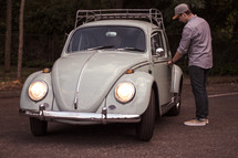 a man opening the door of a vintage Volkswagen Beetle