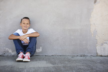 portrait of a child sitting on a sidewalk