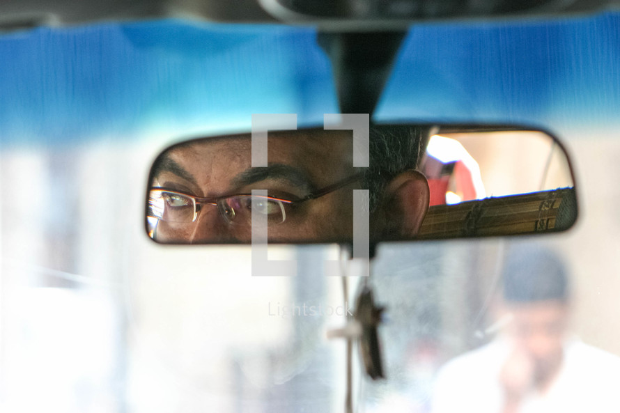 view of a taxi driver in the mirror of a car