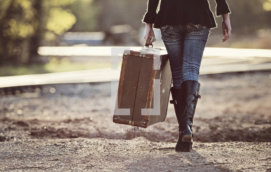 a woman walking on a dirt road carrying a suitcase
