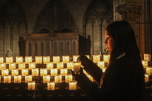 a woman lighting a prayer candle in a cathedral