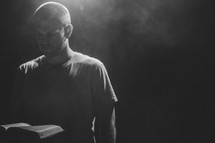 minister reading from a Bible under a spotlight