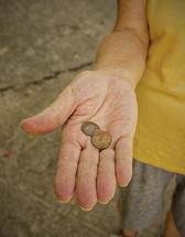 Hand holding pennies.