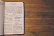 Bible on a wooden table open to the book of 1 John.