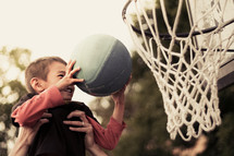 father lifting his son up to put a basketball in the net