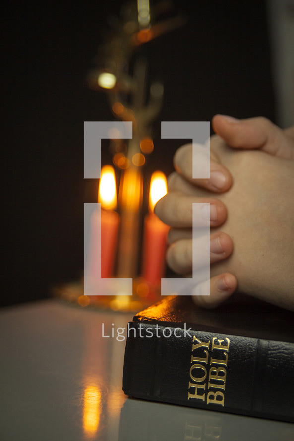 praying handis over a Bible and candles