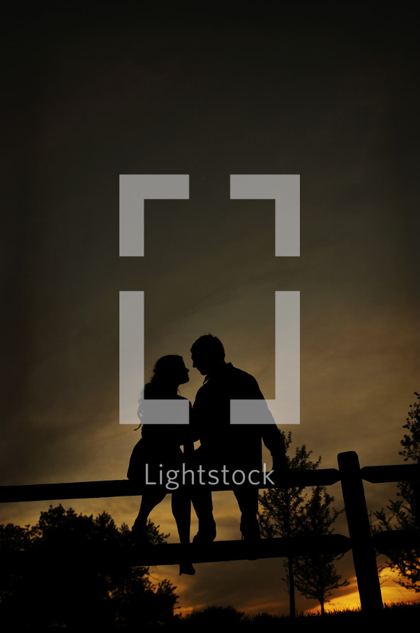 Couple sitting on a fence post embracing at sunset.
