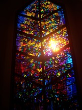 Stained glass window to Heaven with blue, red, yellow, purple colors in a small church chapel.