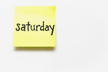 "A yellow sticky note with ""saturday"" written in black ink."