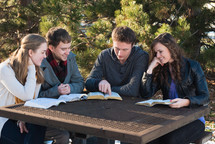 college students sitting at a picnic table reading from Bibles during a Bible study