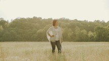 carefree woman walking through a field