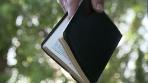 a man holding a Bible in sunlight