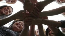 Shot from beneath - a group of friends putting their hands together as in a huddle, then pans down the line of the people holding hands
