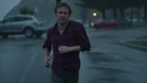 a man running outdoors in the rain in slow motion