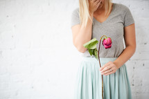 a woman holding a wilting rose