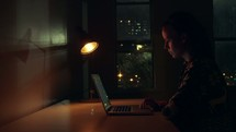 a woman looking at the internet at night in a dark apartment