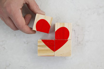building a red heart out of wood blocks.