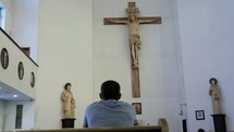 a man in prayer at church in front of an altar