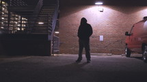 a young man looking down at the ground standing in a parking lot at night