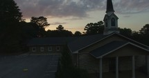 a church parking lot at sunset and an aerial tour over a neighborhood