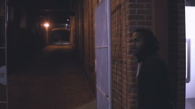 a man walking down a dark alley at night