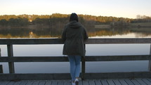 a woman looking over a railing at a lake
