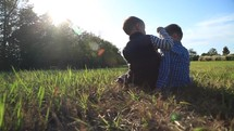 brothers sitting in a grass in a field outdoors talking
