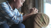 a praying child sitting on a chair