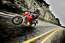 A man on a motorcycle races down the highway