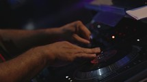 DJ's hands on a sound board.