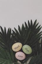 Faith, hope, Love easter eggs on palm leaves