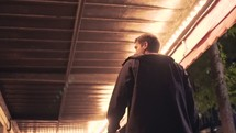 a man walking under a covered walkway at night