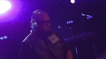 a DJ with headphones at a concert