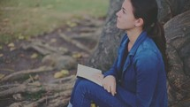 teen girl sitting under a tree reading a Bible
