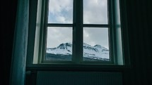 looking through a window at clouds moving over a mountain