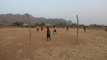 kids playing soccer on a dirt field