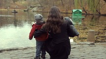 mother and son standing at the edge of a pond