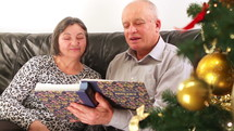 Elderly couple talking near a Christmas tree and looking at a photo album