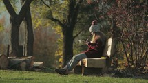 a teen girl sitting on a bench reading a Bible